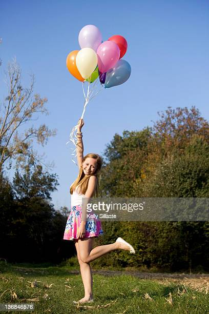 Happy girl holds bouquet of colorful balloons