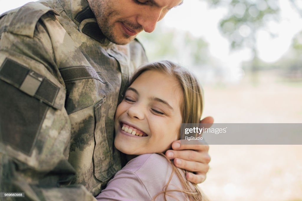 Happy girl hugging a soldier : Stock Photo