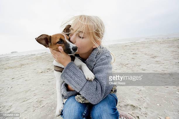 Happy girl hugging dog on the beach