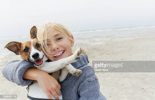 happy girl hugging dog on the beach, portrait - linda oliver fotografías e imágenes de stock