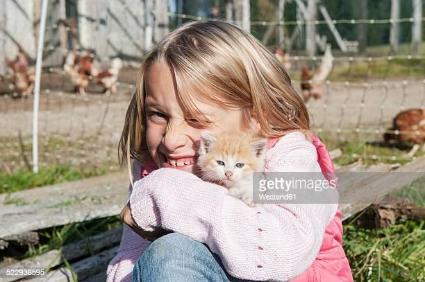 Happy girl hugging kitten