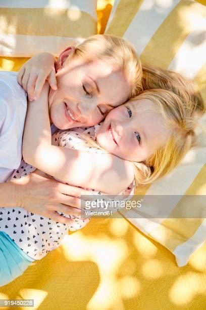 Happy girl hugging mother on a blanket