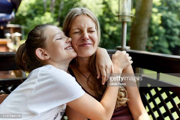 happy girl hugging mother on terrace - pre adolescent child stock pictures, royalty-free photos & images