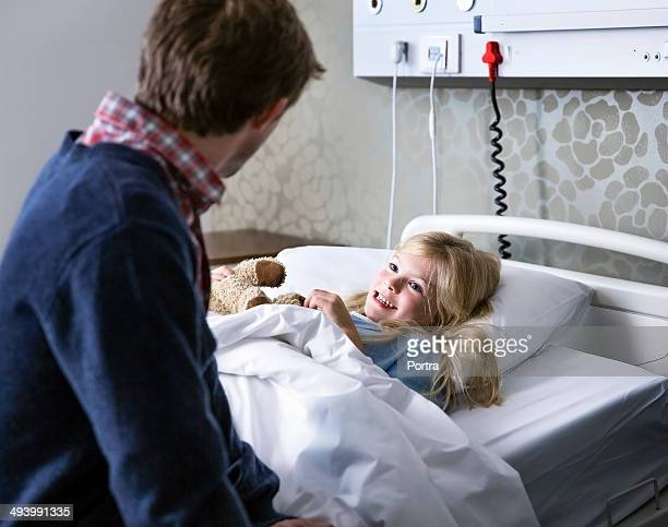 happy girl in a hospital bed talking to her dad. - girl in hospital bed sick stock photos and pictures