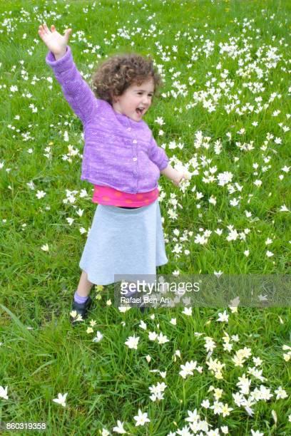 Happy girl in flowers field