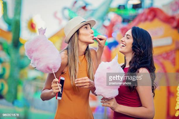 happy girl is feeding her girlfriend with cotton candy at a fun fair - cotton candy stock pictures, royalty-free photos & images