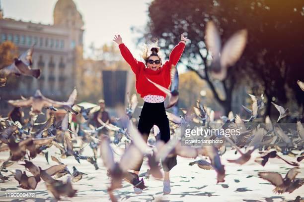 幸せな女の子は喜びから飛び降りています - 翼を広げる ストックフォトと画像