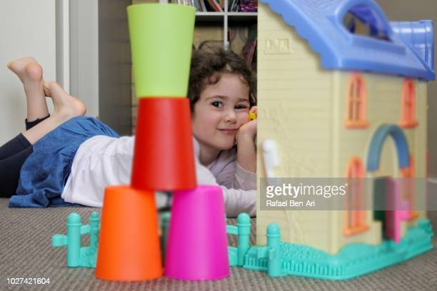 happy girl is playing with a doll house at home - rafael ben ari bildbanksfoton och bilder