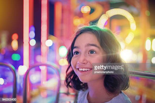 happy girl is smiling on ferris wheel in an amusement park - impressionante foto e immagini stock