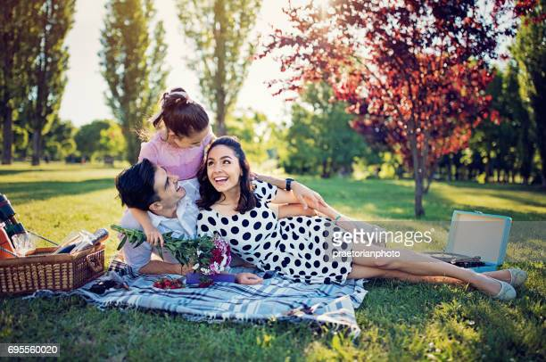 Happy girl is surprising her mother with flowers at picnic in the park