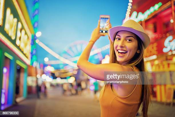 happy girl is taking pictures with her mobile phone in a funfair - multi colored hat stock pictures, royalty-free photos & images