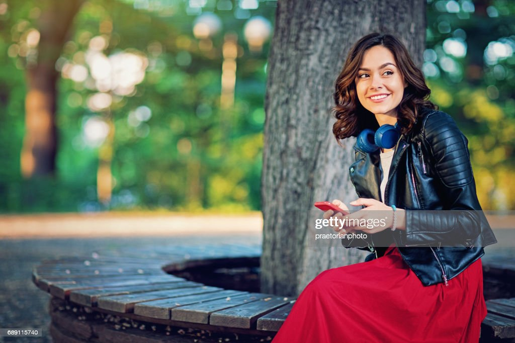 Happy girl is texting in the park and waiting her date : Stock Photo