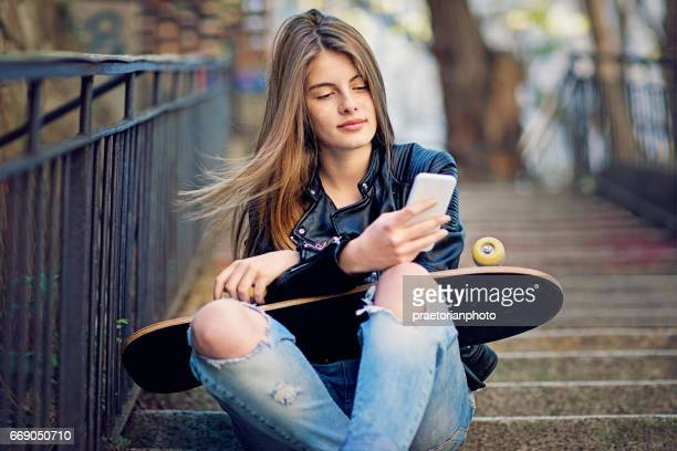 Happy girl is texting on the stairs