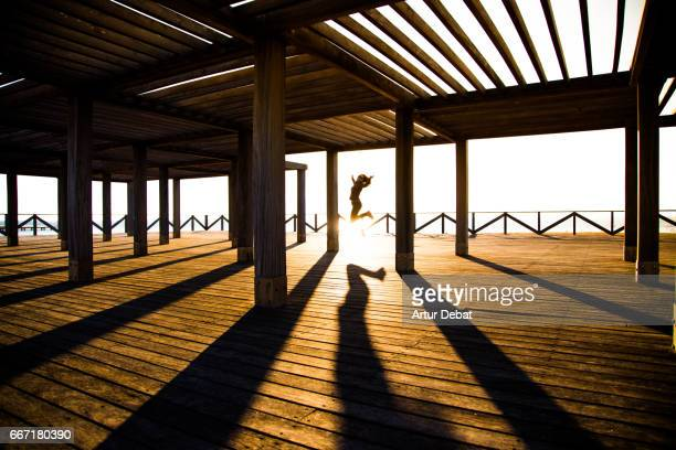 Happy girl jumping in a beautiful environment in the wood dock in front of the Mediterranean Sea in Ebro Delta with nice sunset light and playing with shadows during weekend travel.