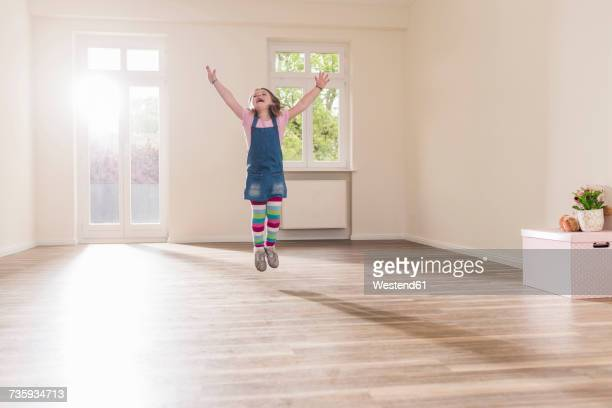 Happy girl jumping in empty apartment