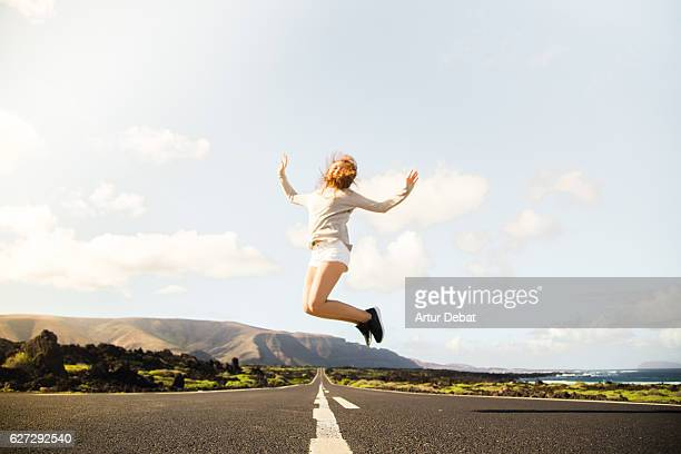 Happy girl jumping on a beautiful long straight road in the volcanic island of Lanzarote during a travel vacations.