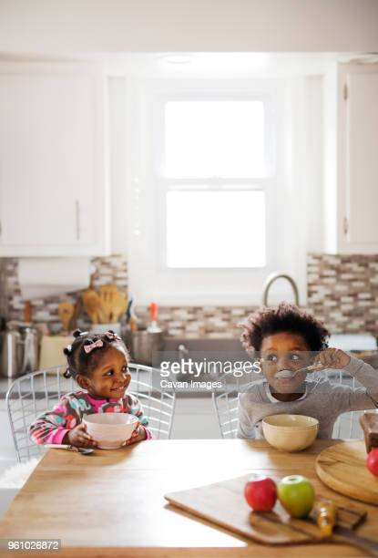 happy girl looking at brother having breakfast in kitchen - sister stock pictures, royalty-free photos & images