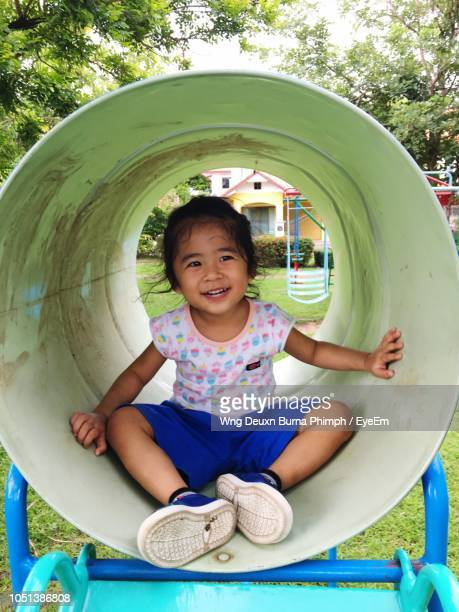 Happy Girl Looking Away While Sitting In Outdoor Play Equipment