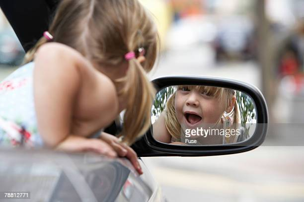 Happy Girl Looking in Side Mirror