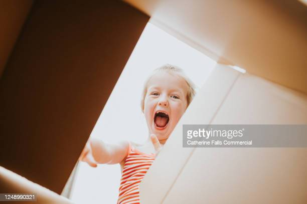 happy girl looking into a box - facial expression stock pictures, royalty-free photos & images