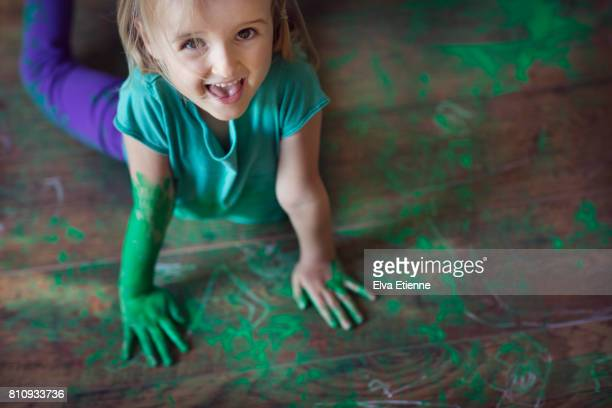 Happy girl (4-5) lying in a mess of green paint on a wooden floor