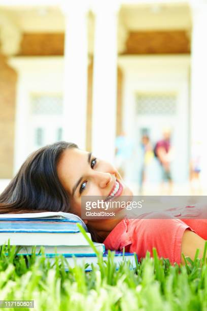 Happy girl lying on campus ground