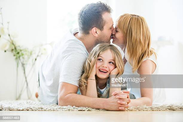 Happy girl lying on floor, parents kissing