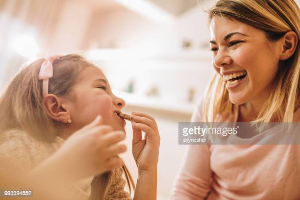 happy girl making her mother laugh while eating a cookie at home. - biscuit stock photos and pictures