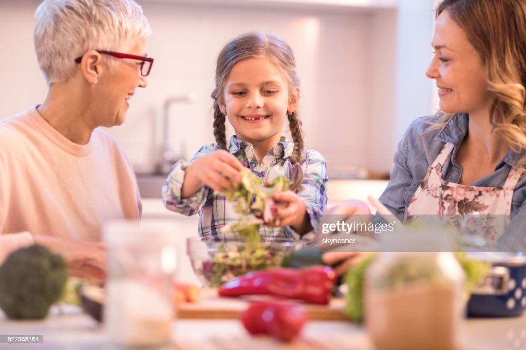 Happy girl making salad with her mother and grandmother. : Stock Photo