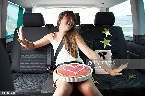 Happy girl n car with heart-shaped cake