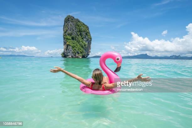 fille heureuse sur flamingo flottant sur l'eau claire en thaïlande - flamant rose photos et images de collection
