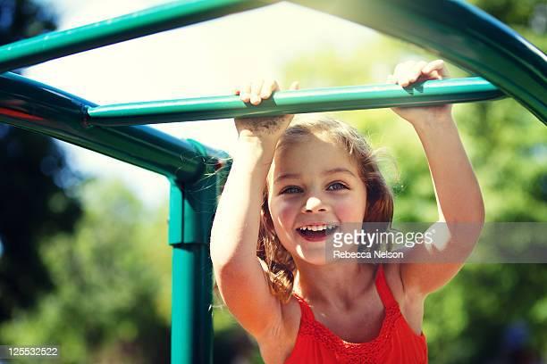 Happy girl on monkey bars