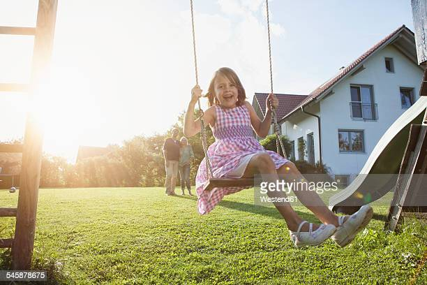 Happy girl on swing in garden