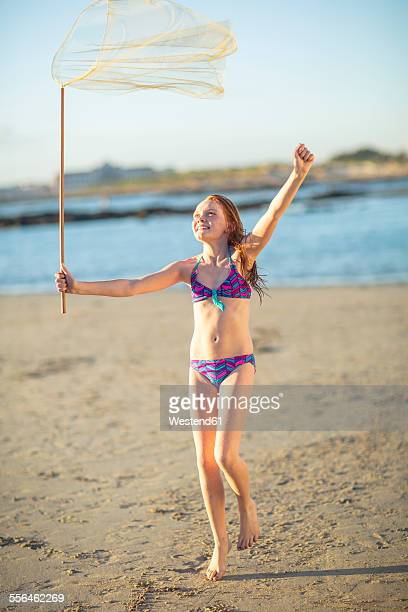 happy girl on the beach running with a butterfly net - redhead girl stock photos and pictures