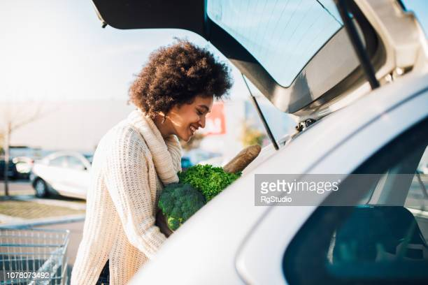happy girl packing groceries - car trunk stock pictures, royalty-free photos & images