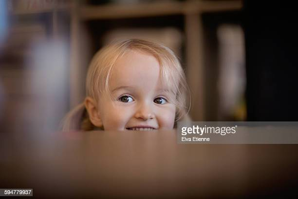 Happy girl peeking over table