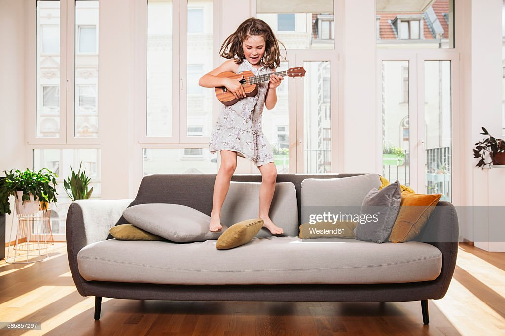 Happy girl playing mini guitar while jumping on a couch in living room at home : Stock-Foto