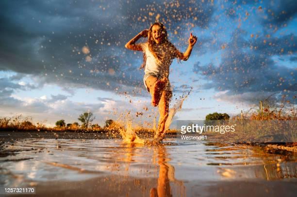 happy girl playing while splashing water on puddle against cloudy sky - somente crianças imagens e fotografias de stock