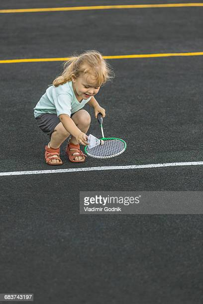 Happy girl playing with badminton racket and shuttlecock on playground