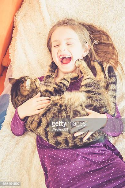 Happy girl playing with cat