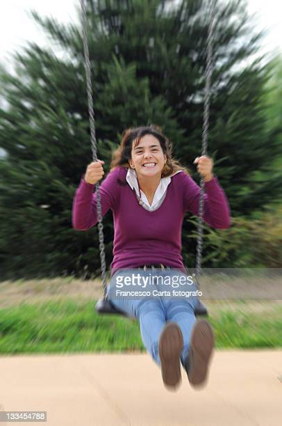 Happy girl plays on swing.