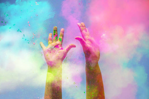 happy girl raising arms with the colorful powder splash during celebration. - 彩色影像 個照片及圖片檔