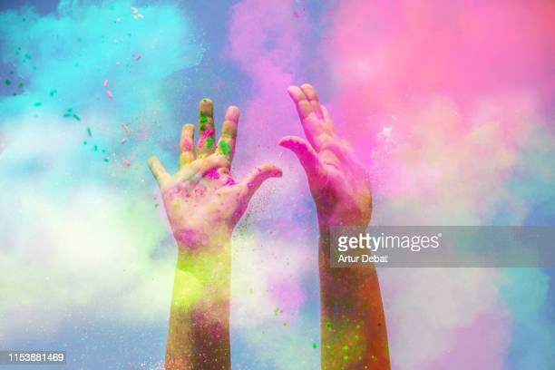 happy girl raising arms with the colorful powder splash during celebration. - comemoração conceito imagens e fotografias de stock