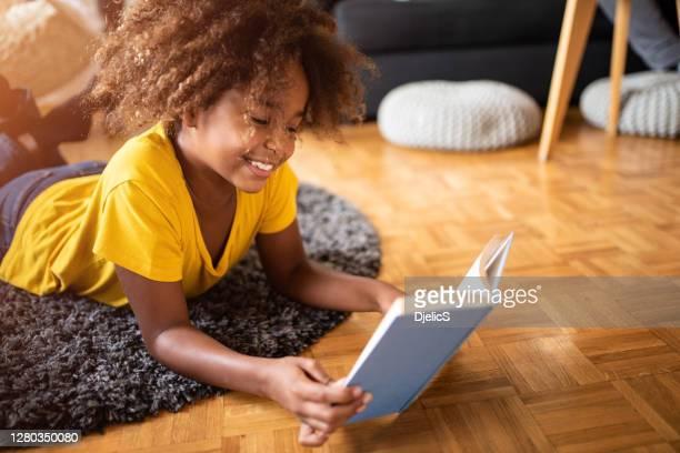garota feliz lendo um livro na sala de estar. - ler - fotografias e filmes do acervo