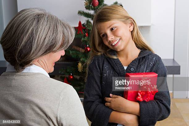 Happy girl receiving Christmas present from granny