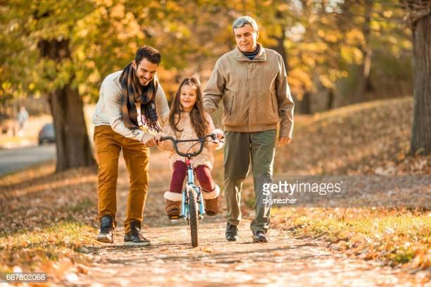 Glückliches Mädchen Reiten Fahrrad mit Hilfe von ihrem Vater und Großvater.
