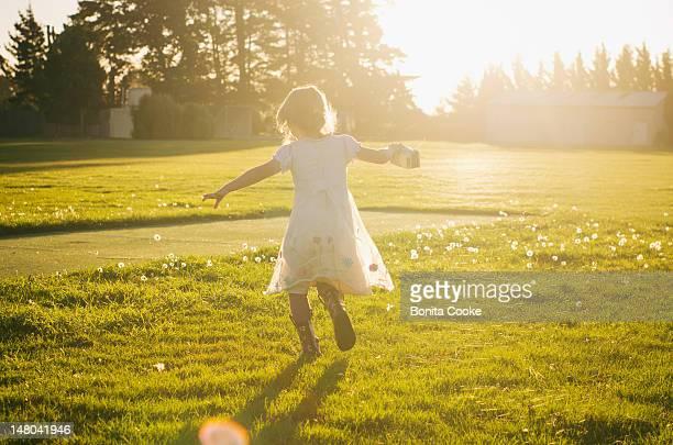 Happy girl running in dandelion field