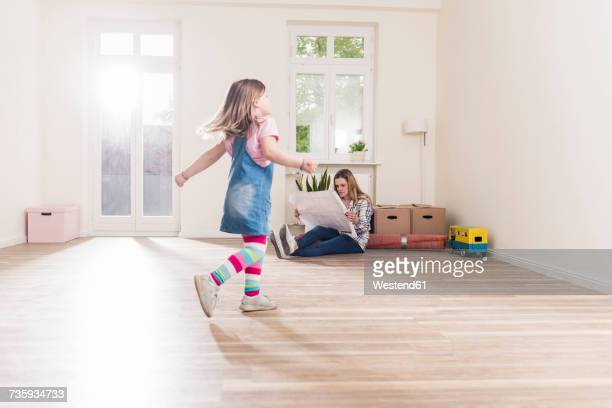 Happy girl running in empty apartment with mother reading plan