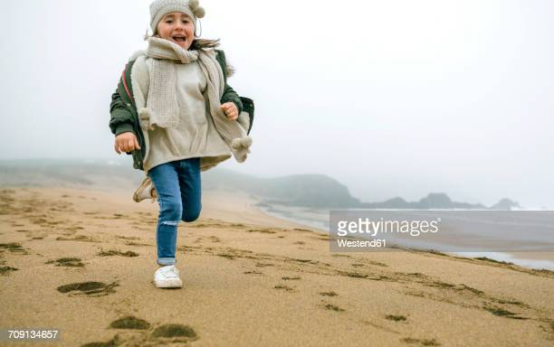Happy girl running on the beach on a foggy winter day