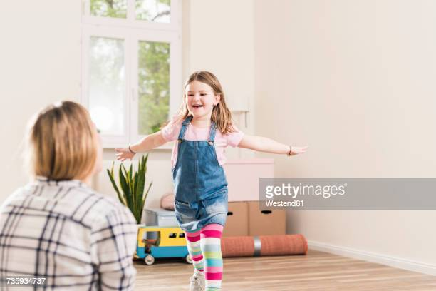 Happy girl running towards mother in empty apartment